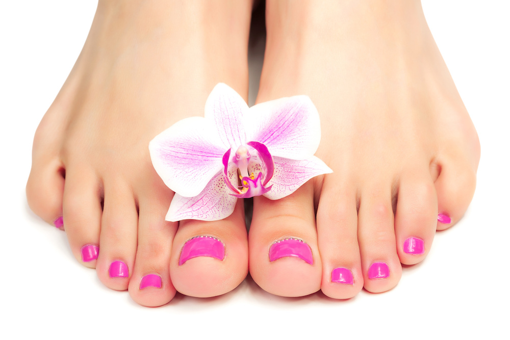 Pink pedicure with a orchid flower on womans feet
