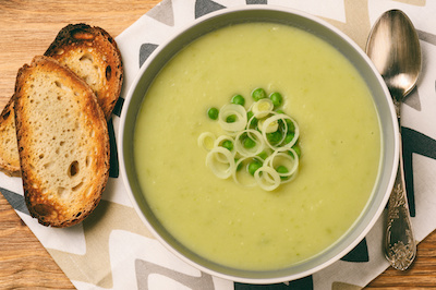 potato leek soup in a bowl with toasted bread and spoon
