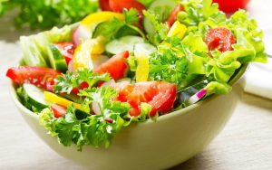 Bowl of delicious green salad with tomatoes and cucumbers