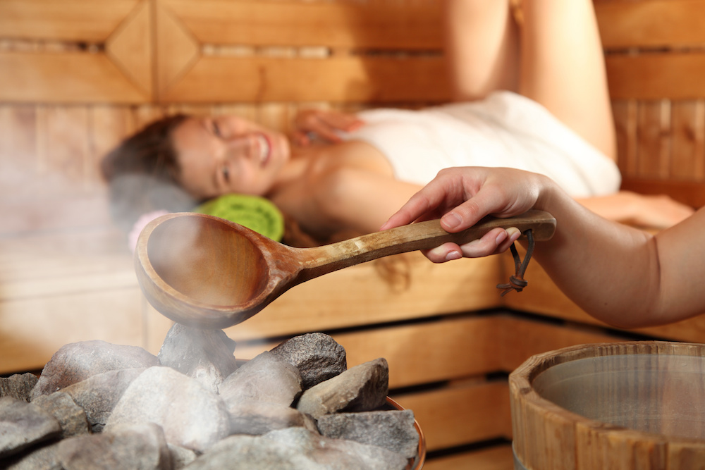 Woman laying in sauna with hand pouring water on sauna stones creating steam at spa