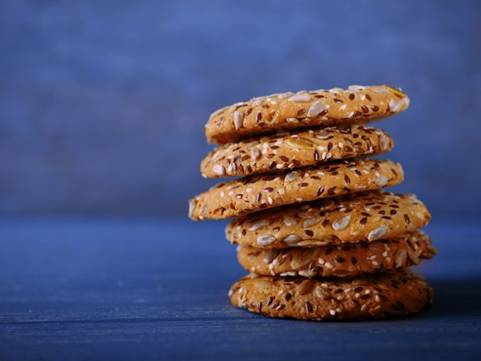 Delicious cereal cookies on color background