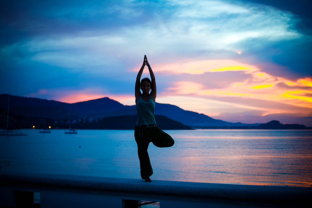young woman doing yoga exercise on the background of amazing sunset.